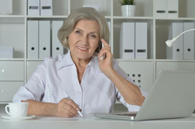 Szczęśliwa starsza kobieta pracująca na laptopie i rozmawiająca przez telefon w biurze