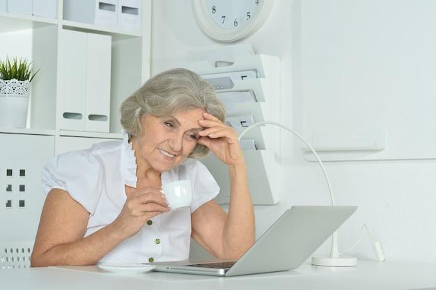 Szczęśliwa starsza kobieta pracująca na laptopie w biurze