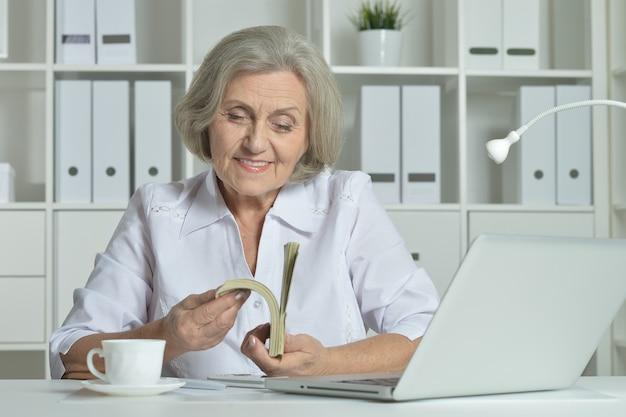 Szczęśliwa starsza kobieta pracująca z laptopem i pieniędzmi w biurze