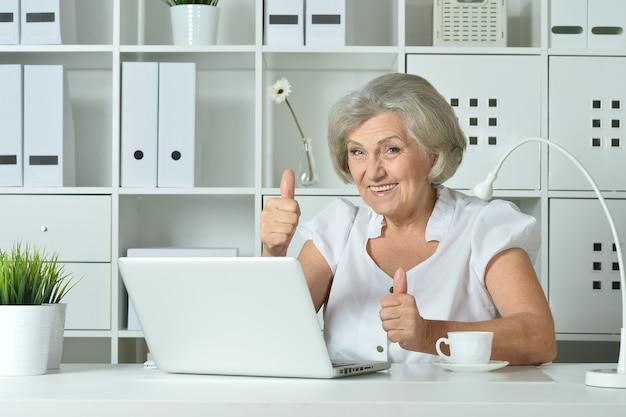 Szczęśliwa starsza kobieta pracuje na laptopie z kciukami do góry w biurze