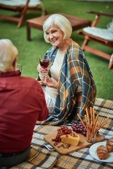 Szczęśliwa starsza kobieta rozmawiająca z mężem i trzymająca wino