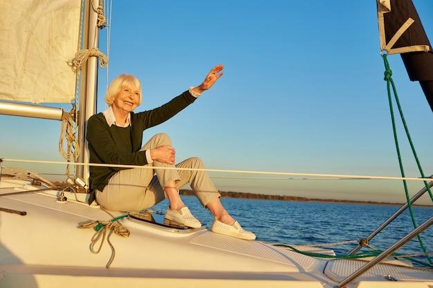 Szczęśliwa starsza kobieta siedząca z boku żaglówki lub pokładu jachtu unoszącego się w spokojnym błękitnym morzu