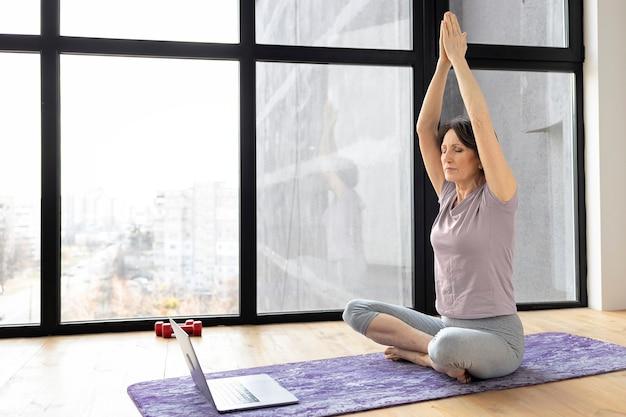 Szczęśliwa starsza kobieta siedzi na podłodze w pozycji lotosu, ćwicząc jogę online za pomocą laptopa w domu