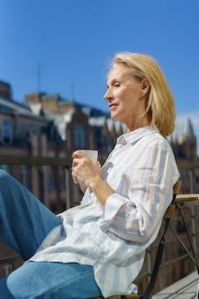 Szczęśliwa starsza kobieta siedzi na tarasie z filiżanką kawy i cieszy się pięknym słonecznym porankiem