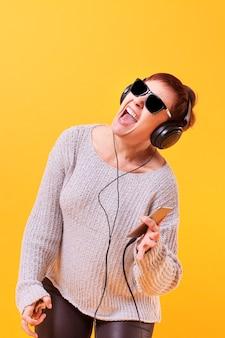 Szczęśliwa starsza kobieta słucha muzykę i tana