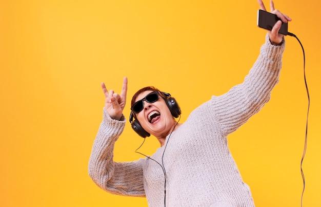 Szczęśliwa starsza kobieta słucha muzykę rockową