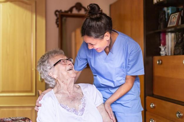 Szczęśliwa starsza kobieta śmia się z jej opiekunem w domu
