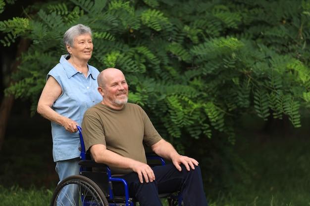 Szczęśliwa starsza kobieta spaceru z niepełnosprawnym starszy mężczyzna siedzi na wózku inwalidzkim na zewnątrz