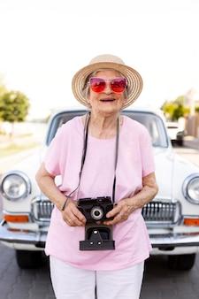 Szczęśliwa starsza kobieta stojąca obok swojego samochodu