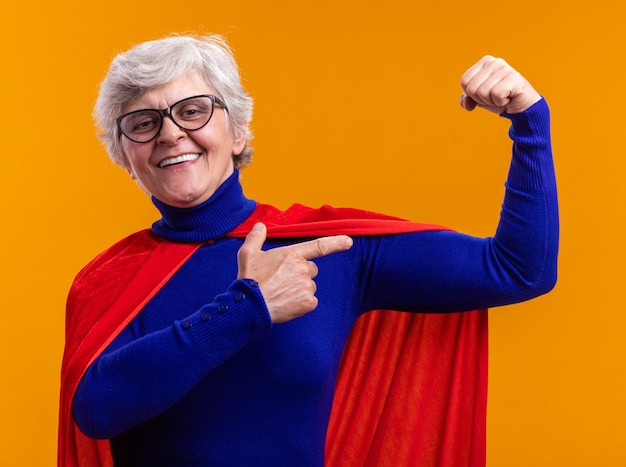 Szczęśliwa starsza kobieta superbohater w okularach w czerwonej pelerynie pozowanie przed kamerą podnoszącą pięść jak zwycięzca pokazujący biceps stojący na pomarańczowym tle