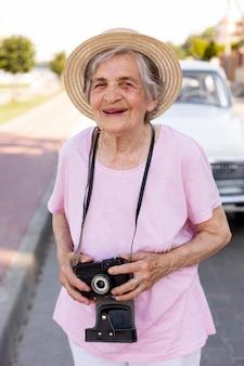 Szczęśliwa starsza kobieta trzyma aparat podczas podróży