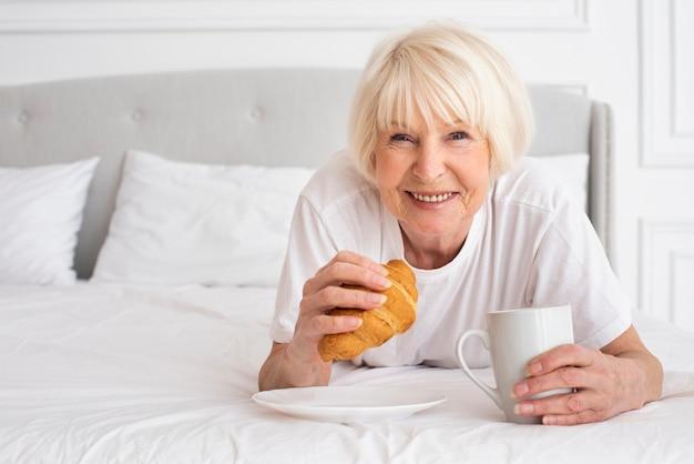 Szczęśliwa starsza kobieta trzyma filiżankę i rogalika