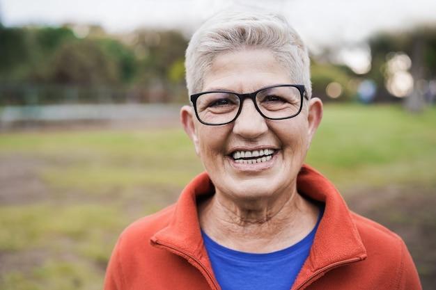 Szczęśliwa starsza kobieta uśmiechając się do kamery na zewnątrz w parku miejskim
