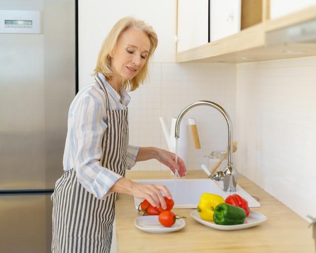 Szczęśliwa starsza kobieta w fartuchu przygotowuje warzywa na sałatkę podczas gotowania w nowoczesnej kuchni w domu