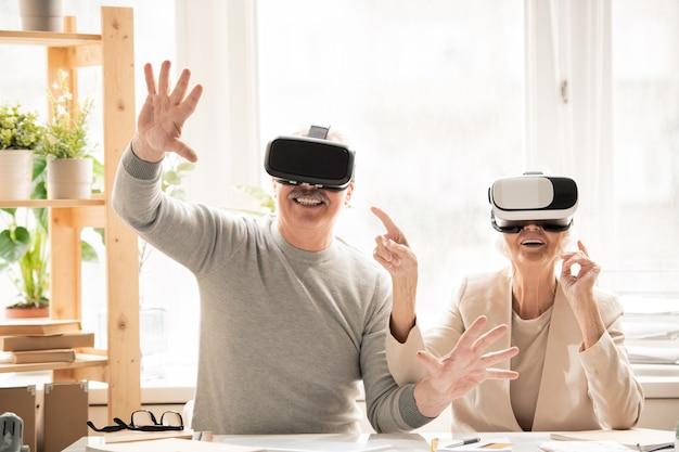 Szczęśliwa starsza kobieta w goglach vr wskazująca na męża w słuchawkach, jednocześnie dotykając wirtualnych rzeczy