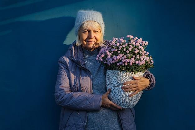 Szczęśliwa starsza kobieta w odzieży wierzchniej uśmiecha się do kamery i niesie kwiaty doniczkowe