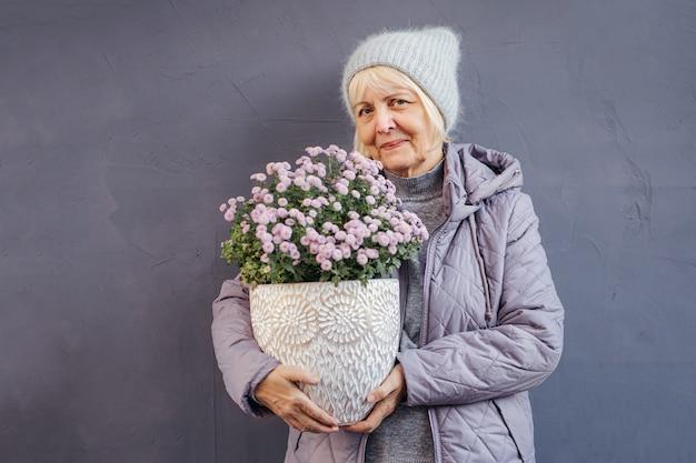 Szczęśliwa starsza kobieta w odzieży wierzchniej, uśmiechając się do kamery i niosąc kwiaty doniczkowe na dzień wiosny.