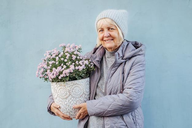 Szczęśliwa starsza kobieta w odzieży wierzchniej uśmiechnięta i niosąca kwiaty doniczkowe na dzień wiosny.