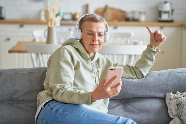 Szczęśliwa starsza kobieta w słuchawkach słucha muzyki na smartfonie, relaksując się w domu na kanapie