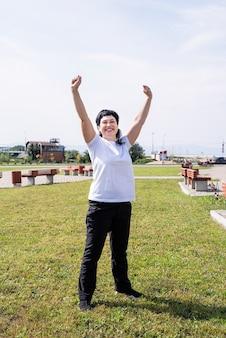 Szczęśliwa starsza kobieta w strojach sportowych ćwiczeń w parku stojąc z rękami do góry