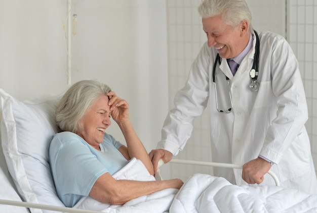 Szczęśliwa starsza kobieta w szpitalu z troskliwym lekarzem