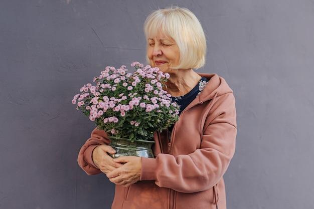 Szczęśliwa starsza kobieta wącha kwiaty. wesoła starsza kobieta w zwykłych ubraniach uśmiechnięta