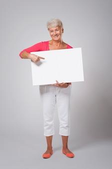 Szczęśliwa starsza kobieta, wskazując na tablicy