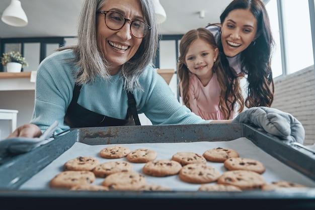 Szczęśliwa starsza kobieta wyjmująca ciasteczka z piekarnika i uśmiechająca się spędzając czas z rodziną