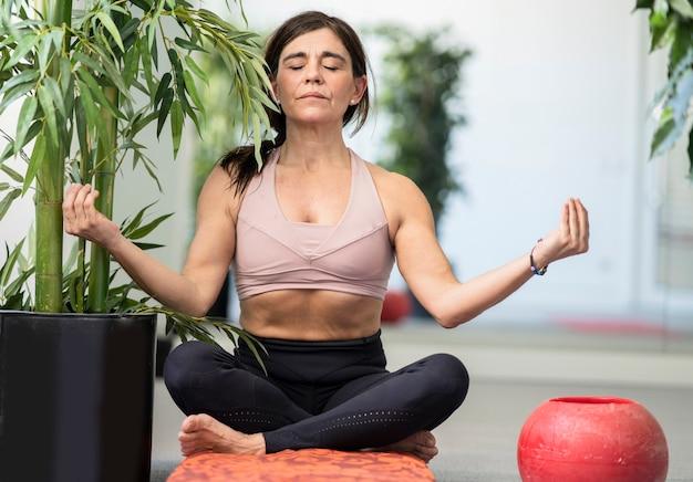 Szczęśliwa starsza kobieta wykonująca jogę w skrzydlatym pokoju do ćwiczeń plant
