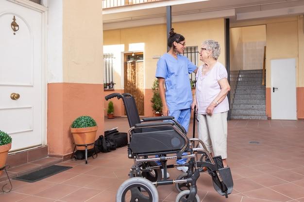 Szczęśliwa starsza kobieta z chodzącym kijem z jej opiekunem w domu