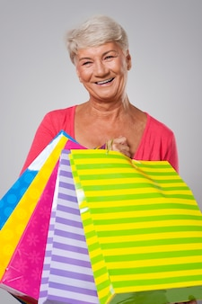 Szczęśliwa starsza kobieta z pełnymi torby na zakupy