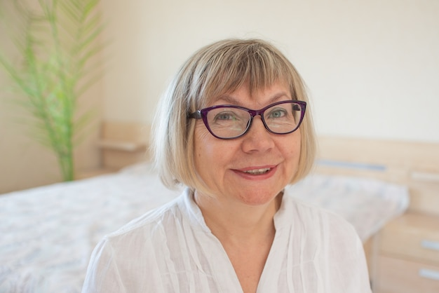 Szczęśliwa starsza kobieta z siwymi włosami relaksujący uśmiech, patrzy na kamerę w sypialni