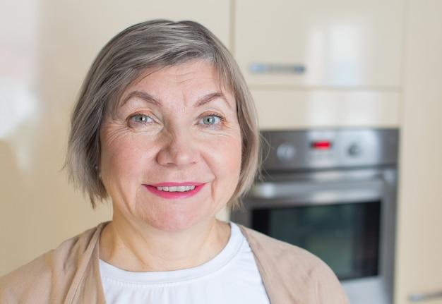 Szczęśliwa starsza kobieta z siwymi włosami w jej kuchni.