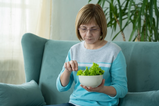 Szczęśliwa starsza kobieta zjada miskę sałatki warzywnej