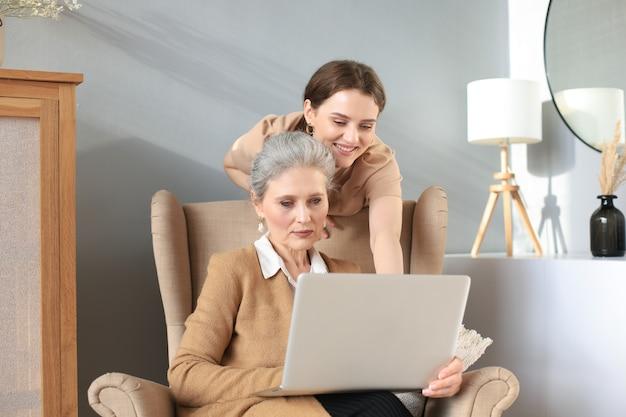 Szczęśliwa starsza matka środkowego siedzi na krześle z córką, patrząc na laptopa. młoda kobieta pokazuje wideo, zdjęcia mamusi, zaufane relacje. koncepcja rodziny.
