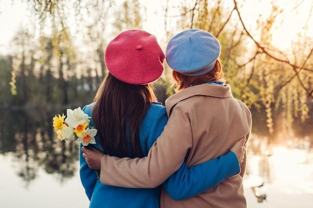 Szczęśliwa starsza matka z kwiatami i jej dorosła córka przytulanie nad rzeką wiosną o zachodzie słońca
