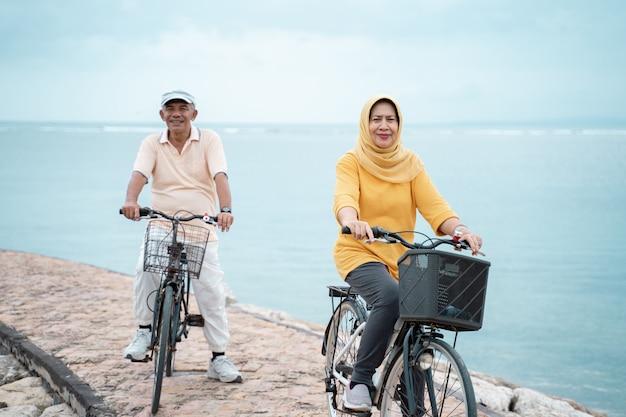Szczęśliwa starsza muzułmańska para ćwiczy jeździeckiego bicykl wpólnie