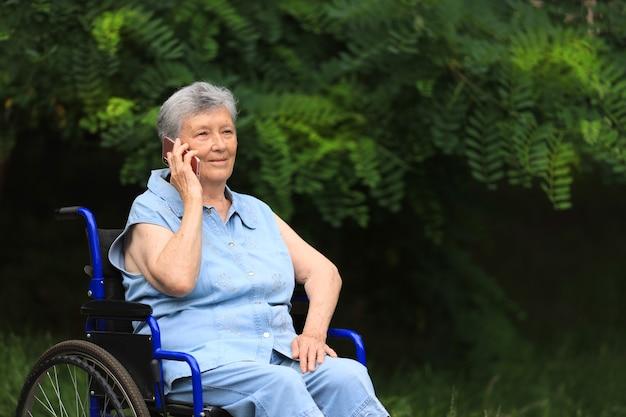 Szczęśliwa starsza niepełnosprawna kobieta siedzi na wózku inwalidzkim na zewnątrz, rozmawia przez telefon
