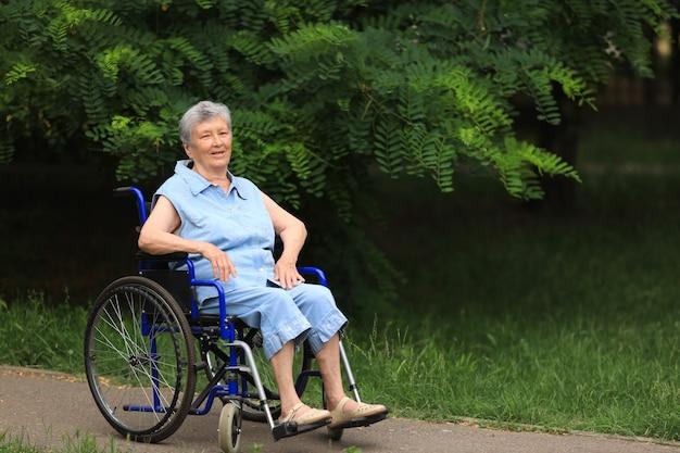 Szczęśliwa starsza niepełnosprawna kobieta siedzi na wózku inwalidzkim na zewnątrz