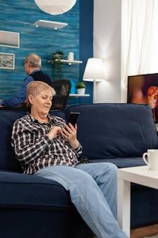 Szczęśliwa starsza pani wysyła sms-y na telefon