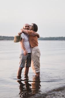 Szczęśliwa starsza para azjatycka kobieta przytulająca męża na brzegu morza na letnie wakacje ujęcie całego ciała