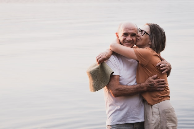 Szczęśliwa starsza para azjatycka kobieta przytulająca męża na brzegu morza na letnie wakacje