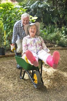 Szczęśliwa starsza para bawić się z taczką