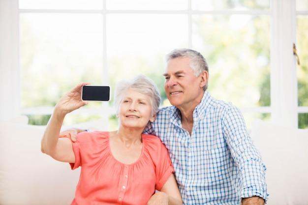 Szczęśliwa starsza para bierze selfie na kanapie