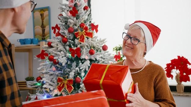 Szczęśliwa starsza para ciesząca się świątecznym dzieleniem prezentu w świątecznej udekorowanej kuchni