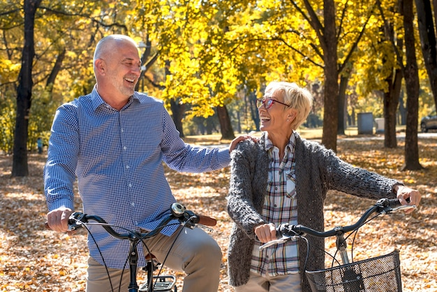 Szczęśliwa starsza para jeździ na rowerze w parku jesienią in