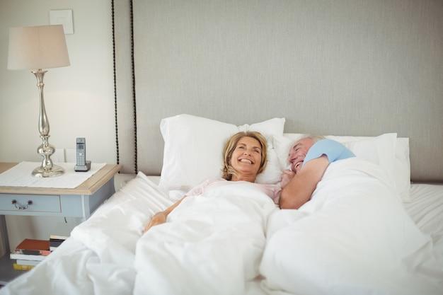Szczęśliwa starsza para leżąc na łóżku