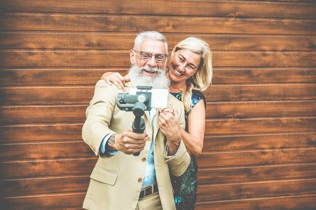 Szczęśliwa starsza para ma zabawę robi wideo z smartphone