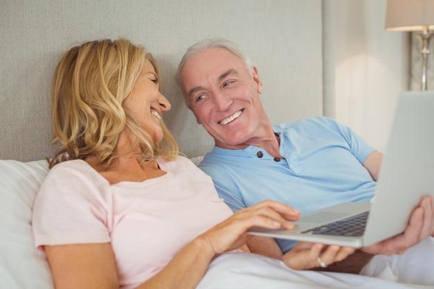 Szczęśliwa starsza para na łóżku za pomocą laptopa