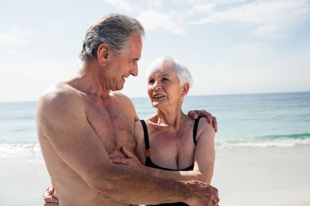 Szczęśliwa starsza para obejmując na plaży